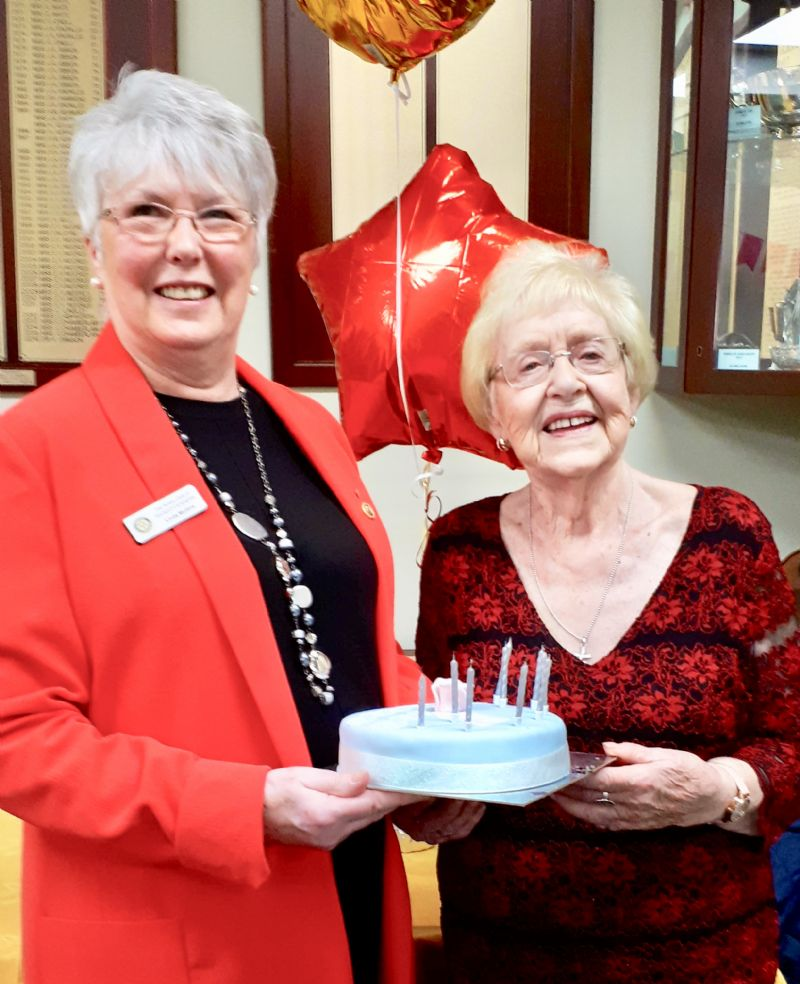 Linda Mullins ( left ) presents a birthday cake to Joan Ebbrell ( right )